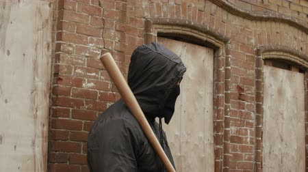 hostility : Street hooligan in black mask with baseball bat on criminal street district looking to camera