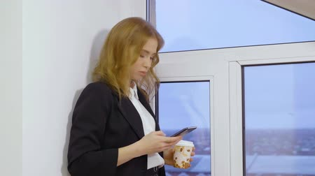 беспроводной : Corporate female manager texting on smartphone and holding disposable cup of coffee near window Стоковые видеозаписи