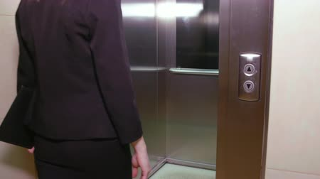 Войти : Serious businesswoman in formal wear coming into elevator in office Стоковые видеозаписи
