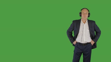 łysy : Bald man in business suit listening music in headphones on green background