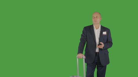 voar : Business man with travel suitcase holding mobile phone on green background
