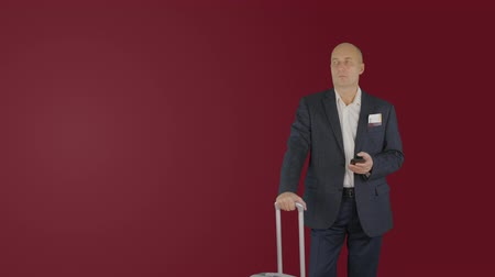 łysy : Traveling businessman with suitcase looking mobile phone on red background