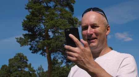 łysy : Smiling man using mobile phone for call by video chat in summer park