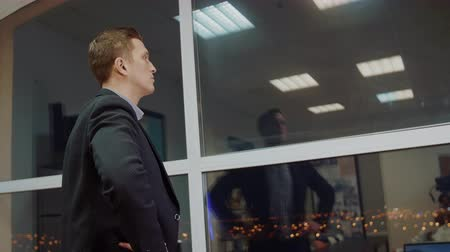 владелец : Back view of male entrepreneur dressed in corporate suit looking out of window while waiting business partner in modern stylish evening office with glass windows. Confident proud CEO in building Стоковые видеозаписи