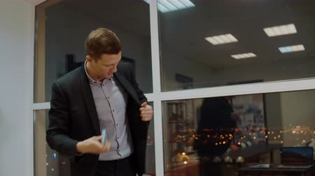зарплата : Satisfied businessman putting money stack in inside pocket of jacket in office Стоковые видеозаписи