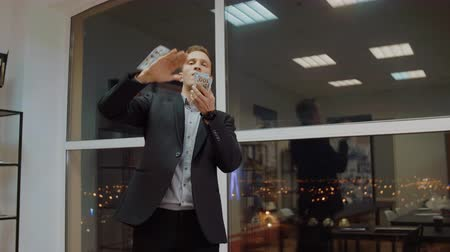 долл : Rich business man throwing out money from stack on office window background