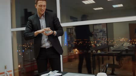 ищу : Cheerful businessman collecting money cash from desktop in evening office