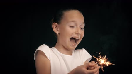 кричать : Scared girl holding in hands burning sparkler with hot sparks on black background Стоковые видеозаписи