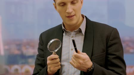 handheld shot : Handsome expert in suit checking pen with magnifier lens, handheld shot