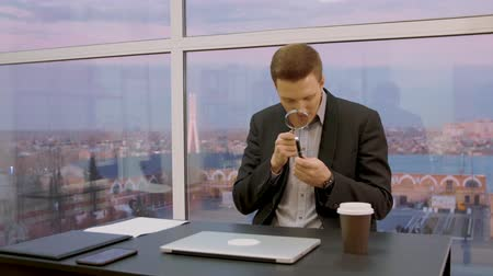 pertavsız : Male expert checking pen with magnifying glass while sitting at workplace