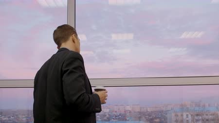 kahve molası : Thoughtful man with coffee to go looking through window at beautiful evening sky and city