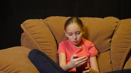 felicidade : Relaxing teenager girl using smartphone in cozy chair in home living room Stock Footage