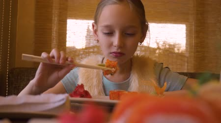 cozinha japonesa : Young girl mouth eat sushi with red salmon. By wooden chopsticks Stock Footage