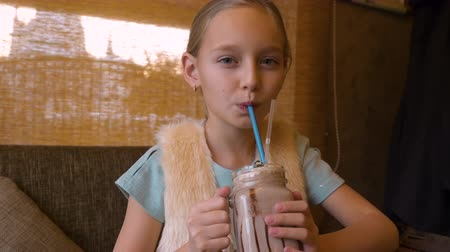 milk shake : Portrait teenager girl drinking milk shake cocktail at table in cafe close up Stock Footage