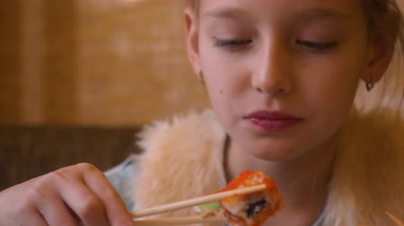 cozinha japonesa : Young teenager girl eating sushi roll with chopsticks in japanese cafe close up