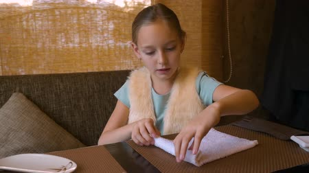 cozinha japonesa : Teenager girl rolling wet cotton napkin on table in sushi restaurant Stock Footage