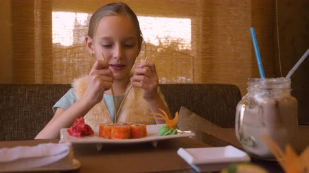 cozinha japonesa : Happy teenager girl spliting chopsticks for eating sushi roll in asian restaurant