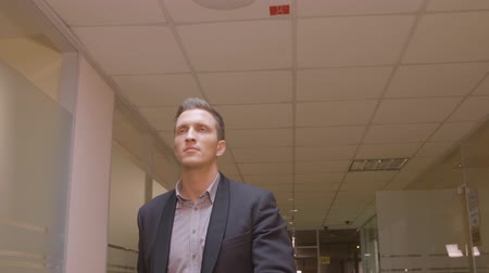 воротник : Handsome businessman in business suit walking in corridor business office. Cheerful manager walking at hall inside modern business office. Business people concept