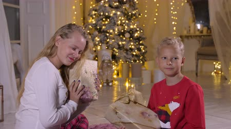darovat : Teenager girl and red boy holding in hands New Year present box on holiday tree background. Happy children with Christmas gifts in cozy living room at holiday eve. Merry Christmas and happy New Year