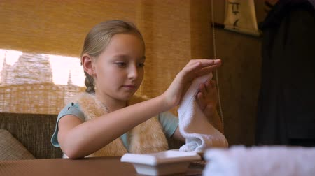 felicidade : Little girl cleaning her hands with wet towel. Cute small girl sitting at the restaurant table, cleaning her hands using napkin whike waiting her meal. Close up cafe restaurante portrait Stock Footage