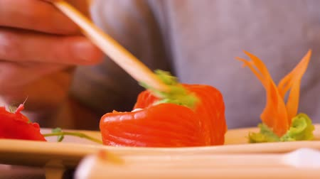 cozinha japonesa : Man eating japanese sushi roll with wasabi in traditional asian restaurant. Japanese sushi with salmon and wasabi in oriental cafe close up. Traditional japanese cuisine red salmon. Food concept Stock Footage