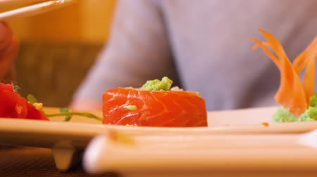 cozinha japonesa : Male hand holding sushi roll with chopsticks and pouring soy sauce in asian restaurant. Man eating japanese sushi roll red fish, red salmon, in traditional resturant. Food concept, asian cuisine