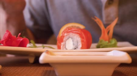 cozinha japonesa : Close up sushi roll in japanese restaurant. Dipping sushi roll in soy sauce in asian restaurant. Traditional asian cuisine, red fish, red salmon, japanese food concept