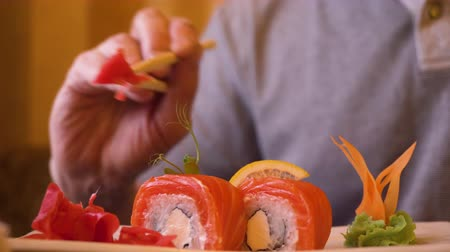 atum : Male hands taking red ginger with wooden chopsticks while eating sushi roll. Man eating traditional sushi roll in japanese restaurant. Food and meal concept. Asian food and snack Stock Footage