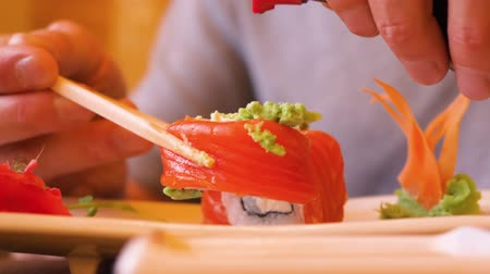 orientalne : Man pouring soy sauce on red sushi roll and eating in traditional japanese restaurant. Man eating japanese red salmon, sushi roll with soy sauce in oriental cafe. Food concept. National asian cuisine