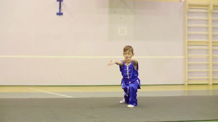 fegyelem : Young boy in national Chinese dress is practicing Kung Fu wushu tai chi Nanquan form. Kung Fu, Nanquan Style. Nanquan strikes of fist called Gua Gai Quan. Nanquan, southern fist nan pai kicks boxing, Stock mozgókép