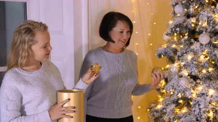 positive vibes : Mom together daughter decorating Christmas tree in living room at holiday eve. Mother with daughter preparing to celebration New Year night in cozy home. Christmas mood and atmosphere