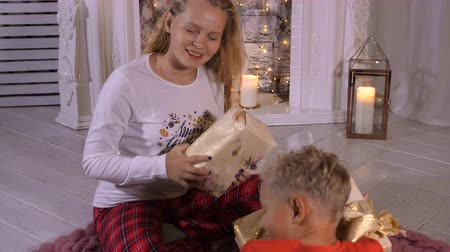 pisos : Happy sister and brother holding in hands Christmas present box near decorative fireplace in living room. Happy girl teenager and boy in red pullover with New Year gifts. Merry Christmas and New Year Stock Footage