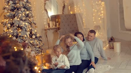 positive vibes : Joking family posing on New Year tree background in cozy home at holiday eve. Happy family mom, father, daughter and son on Christmas tree background in living room. Christmas and New Year atmosphere Stock Footage