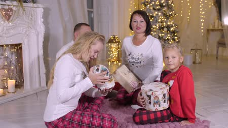 sabah : Christmas family portrait, happy parents daughter and son looking gifts in christmas morning. Christmass portrait happy familly check xmass gift box on christmass tree background. Sits on floor.