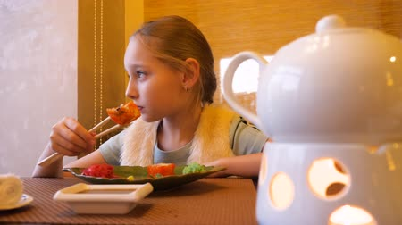 cozinha japonesa : Girl teenager eating japanese sushi roll with chopsticks in restaurant close up. Young teenager girl eating fresh sushi roll in asian restaurant. Asian cuisine and food concept