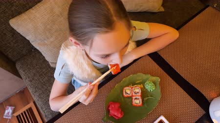 cozinha japonesa : Teenager girl eating red japanese sushi roll with chopsticks in asian restaurant top view. Girl teenager eating traditional sushi roll in japanese cafe. Asian cuisine, food and snack concept overhead