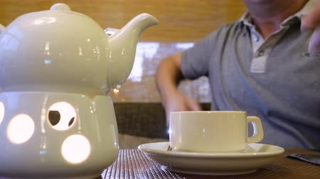 fincan tabağı : Man taking tea pot and pouring hot tea in cup at table in restaurant close up. Male hand holding teapot and pouring tea beverage in white cup in cafe close up