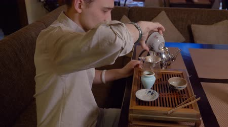 glass pitcher : Tea master preparing chinese tea on brewing table while traditional tea ceremony. Potter man pouring tea infusion from gaiwan to fairness pitcher glass pot with sieve. Traditional ceremony