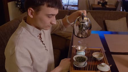 infusion : Tea master pour hot water from kettle to gaiwan with leaves of green tea. Chinese traditional ceremony. Red wood tea boat table. Profile view man brewing oolong tea in yixing clay ceramic gaiwan bowl. Stock Footage
