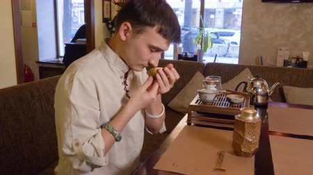 suporte : Man sniffing flavor red tea leaves in chahai during traditional chinese tea ceremony. Profile view man sniff red or green drink before brewing chinese tea. Soft interior light. Profile view.