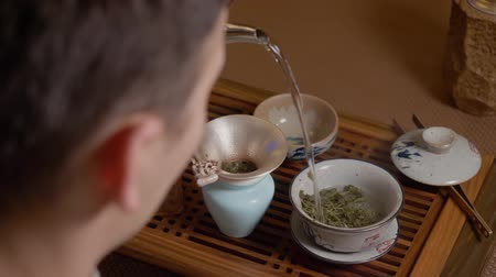 кружка : Tea master pouring hot water from kettle to gaiwan. Steam from hot tea. Handmade tableware made by yixing clay. Traditional Chinese tea ceremony. Shoulders view, POV. Green oolong tea scum Стоковые видеозаписи