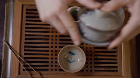 pour out : Tea master pouring tea infusion from gaiwan into fairness pitcher through strainer filter. Man pouring out tea liquor from fairness bowl to bowl. Traditional Chinese tea ceremony red wood. Top down Stock Footage