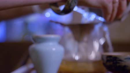 yin and yang : Close up pour out hot tea infusion from gaiwan to fairness pitcher bowl steam rise. Traditional Chinese tea ceremony. Hands tea master preparing tea in yixing clay pottery yin yang sign. Backlight Stock Footage