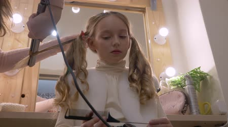 tongs : Beautiful girl while curling long hair with hair iron in hairdressing salon low angle. Hairstylist doing curly hairstyle with hair tongs to girl teenager in beauty salon. Hair style and care