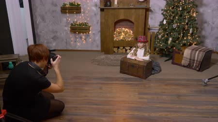 interiér : Professional photographer photographing girl model in Christmas photo studio. Woman photographer directing girl model while photo session. Backstage concept