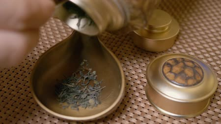 zastawa stołowa : Master pouring dry green tea leaves in bronze chahai while tradition tea ceremony. Close up. Tea ceremony concept. Process preparation chinese tea at table