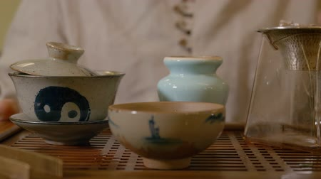 louça de barro : Close up male hand pouring infusion chinese tea from gaiwan to fairness pitcher. Process preparation green tea in pottery from yixing clay. Traditional Chinese tea ceremony Stock Footage