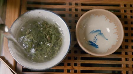 yasemin : Master pouring hot water in bowl with green tea oolong in gaiwan bowl and covering cap top down view. Steam over hot chinese tea cup. Tea master brewing hot jasmine tea infusion at red table. Overhead