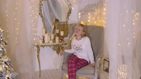 adorável : Happy young girl sitting in armchair. Beautiful teenage girl looking around while sitting in armchair in Christmas eve. Christmass New Year decorated interior