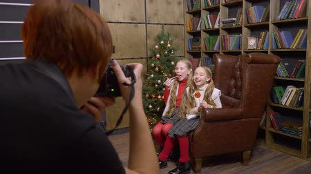 oturum : Baltimore, USA - Desember 25, 2018: photographer working with girls model on Christmas photo session. Photographer joking for laughing girl and taking pictures on New Year photo session Stok Video